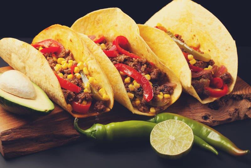 Tre mexicanska taco med finhackade nötkött- och blandninggrönsaker på en svart bakgrund Mexicansk maträtt med avokadot Kryddig oc royaltyfri foto