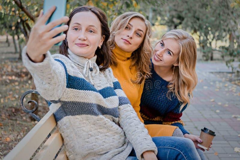 Tre migliori amici attraenti allegri delle giovani donne divertendosi e fare insieme selfie fuori fotografia stock libera da diritti