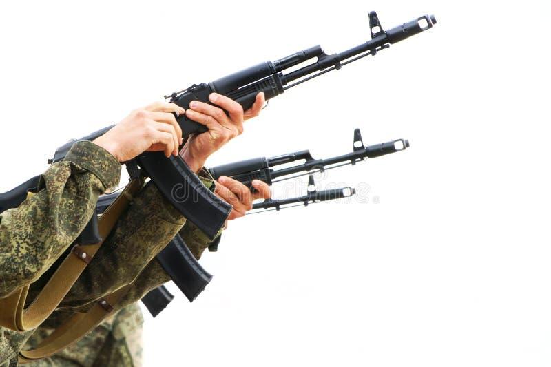 Tre militära maskinartillerister att lägga tillbaka vapen och skjuta på en ljus bakgrund Hot av konflikten royaltyfri fotografi