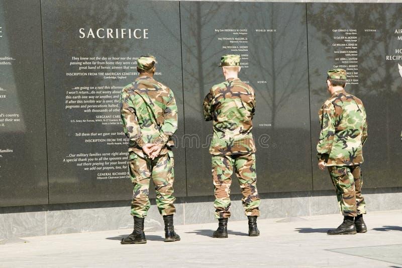 Tre militärer ser granitinskrift på väggen av flygvapenminnesmärken, Arlington, Virginia i Washington D C _ royaltyfri fotografi