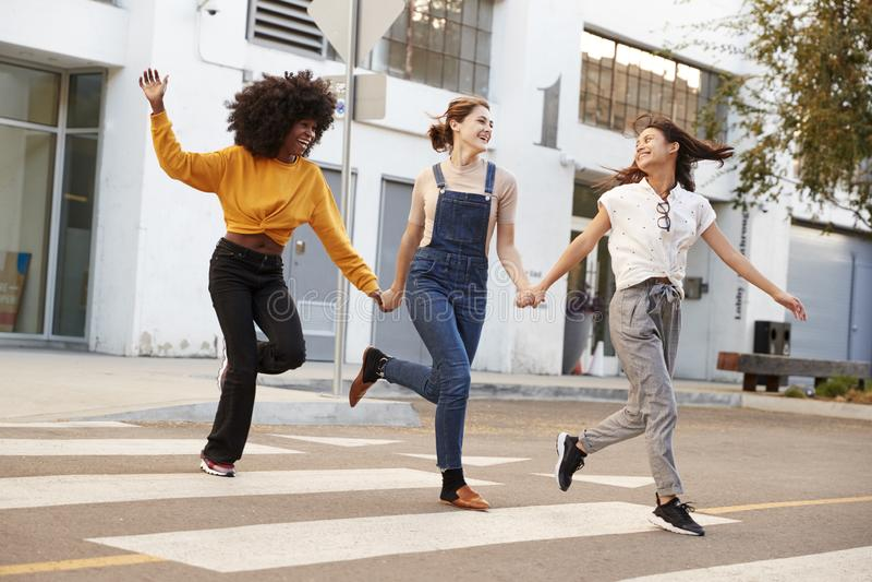 Tre millennial höftflickvänner som rymmer händer och skrattar, som de stöter ihop med en övergångsställe arkivbilder