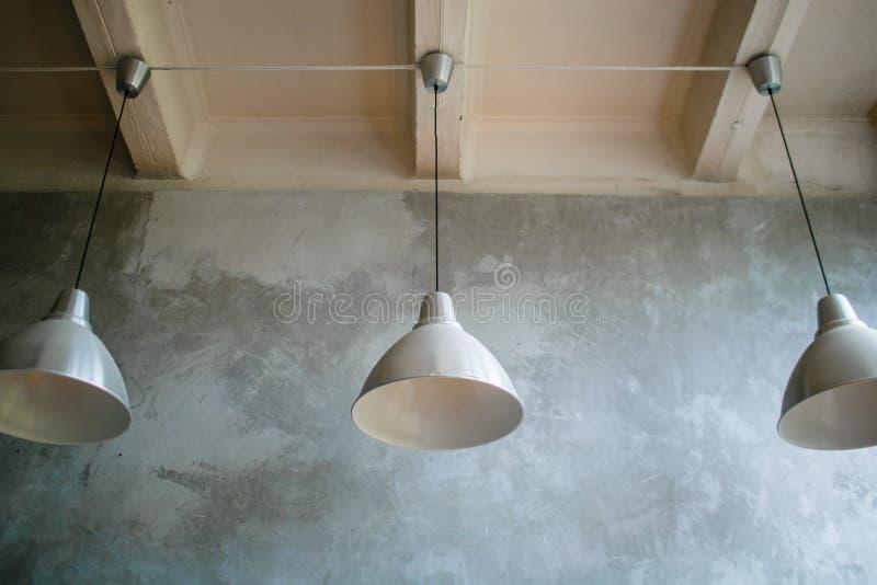 Tre moderna lampor på konkret tak Vit- och silverlampor arkivbilder