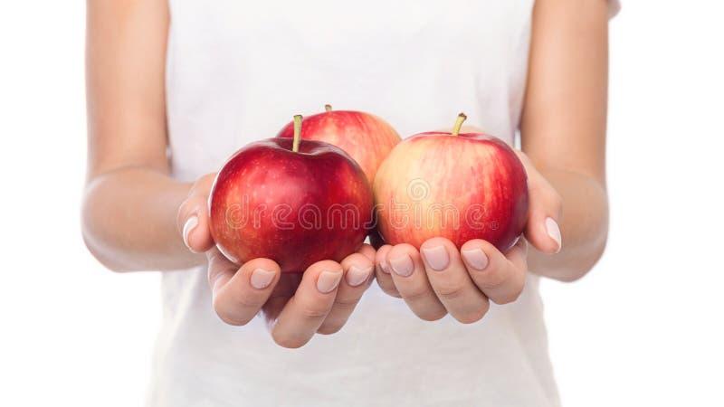 Tre mogna äpplen i kvinnliga händer över vit bakgrund royaltyfria foton