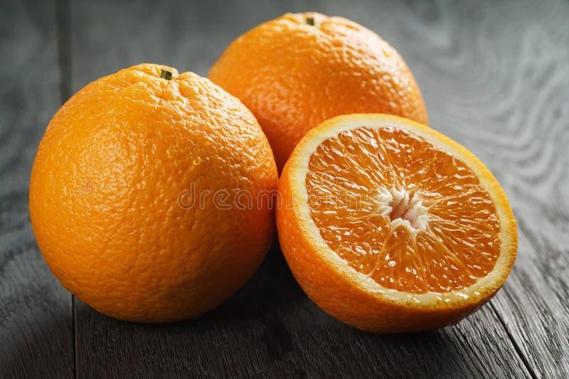 Tre mogna apelsiner på klippt trätabell halvan fotografering för bildbyråer