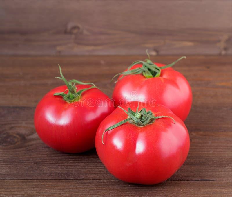 Tre mogna nya röda tomater på träbrun bakgrund arkivfoto