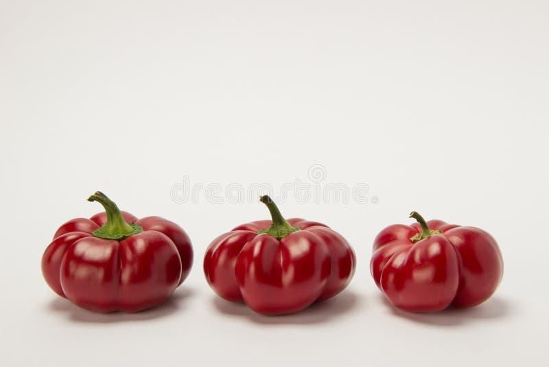 Tre mogna röda söta peppar på en vit bakgrund royaltyfria foton