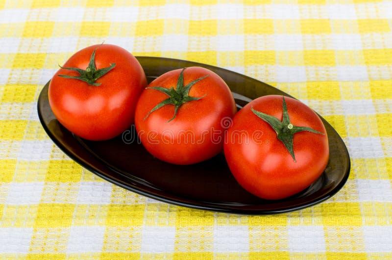 Tre mogna röda tomater i den glass maträtten arkivbild