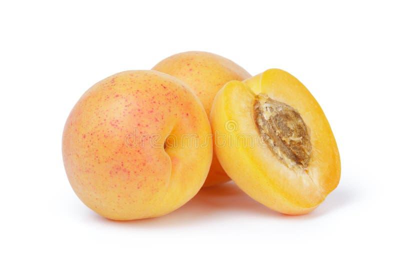 Tre mogna skivade aprikosfrukter halvan isolerat arkivbild