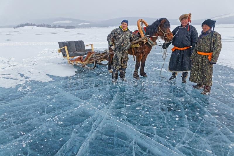 Tre mongoliska män står med en sled på den frusna sjön royaltyfri foto