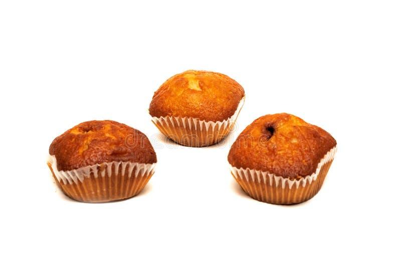 Tre muffin del cioccolato, isolati su fondo bianco immagini stock