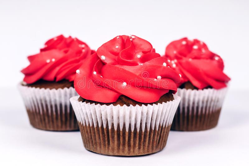 Tre muffin med vibrerande röd isläggning på vit bakgrund Närbild arkivbilder