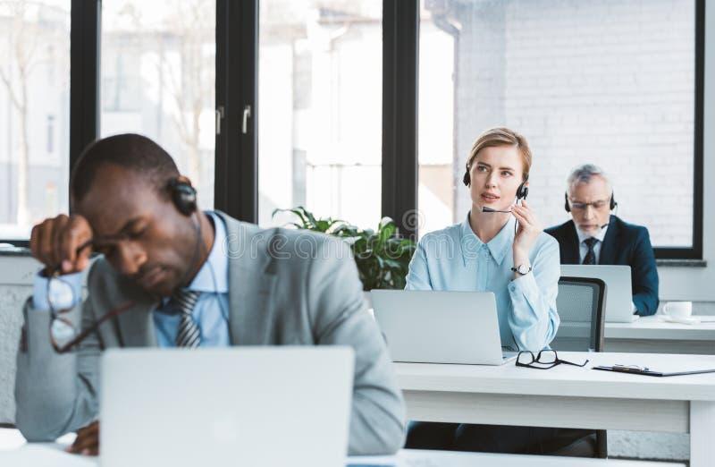 tre multietniska affärspersoner i hörlurar med mikrofon som arbetar med bärbara datorer arkivfoto