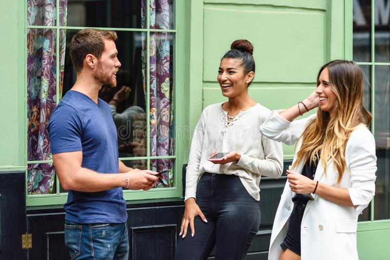 Tre multietniska folkvänner som utomhus skrattar arkivbild