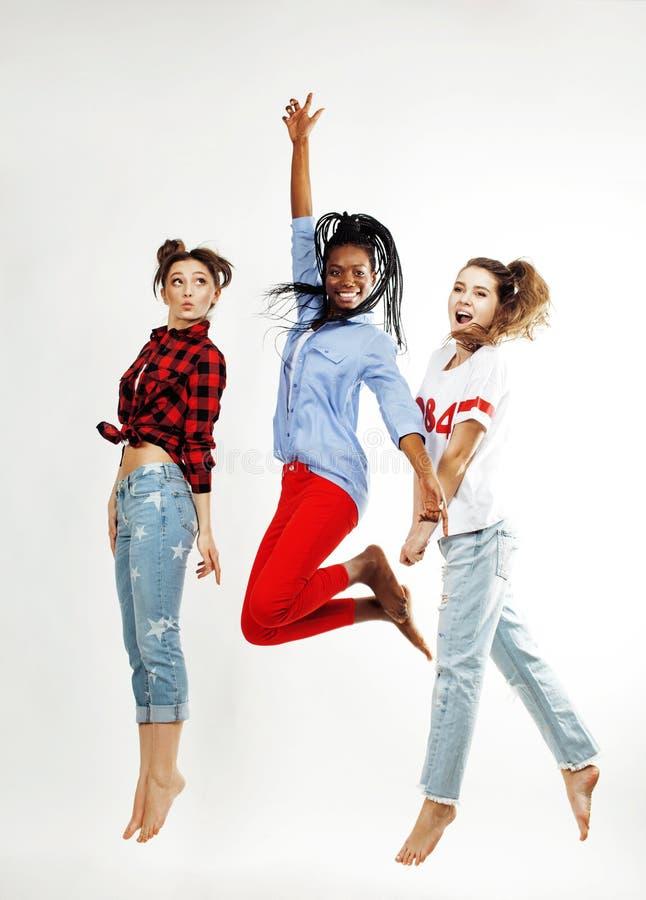 Tre nätt afrikansk amerikan och caucasian, brunett och blonda vänner för tonårs- flicka som hoppar lyckligt le på vit royaltyfri bild