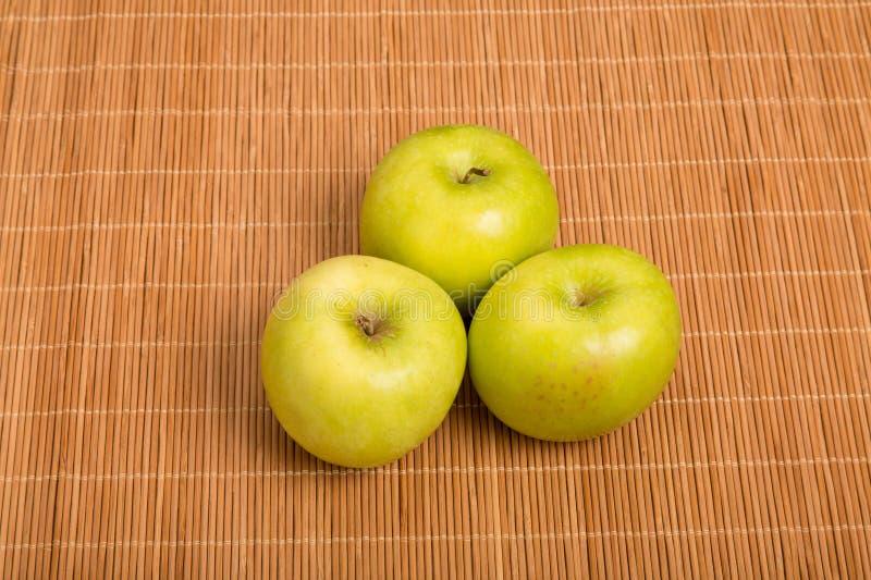 Tre nonna Smith Apples su un Placemat di bambù fotografie stock libere da diritti