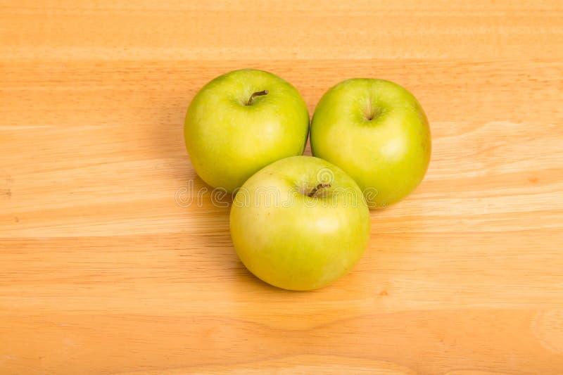 Tre nonna Smith Apples sul contatore di legno immagini stock