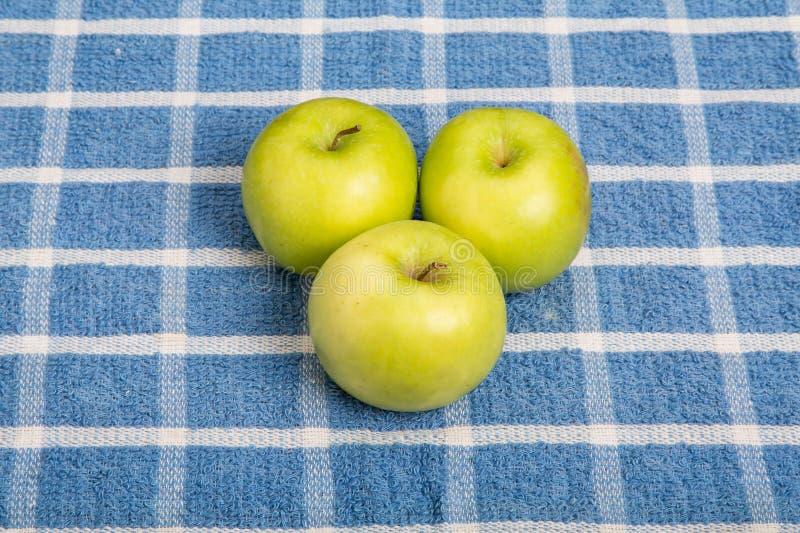 Tre nonna Smith Apples sull'asciugamano blu del plaid fotografia stock