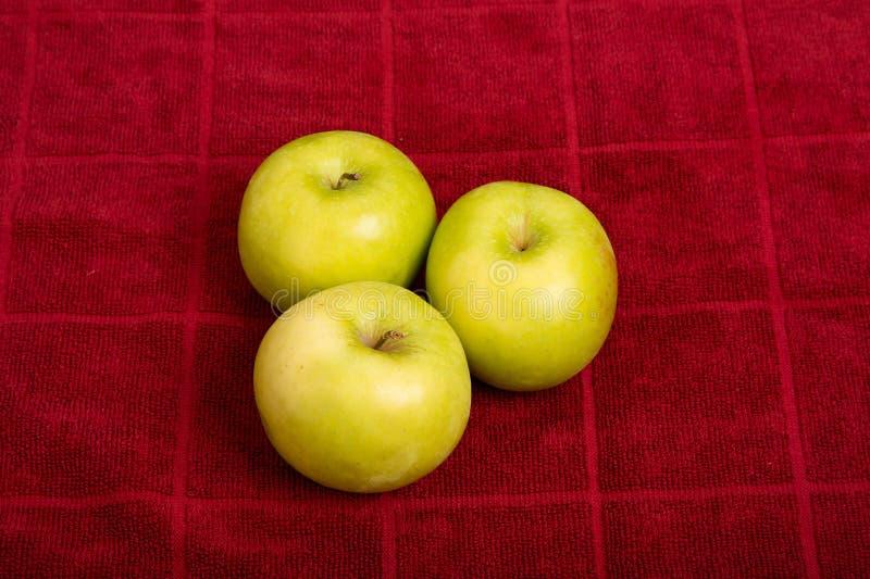 Tre nonna Smith Apples sull'asciugamano rosso immagine stock