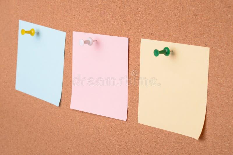 Tre note della carta in bianco sul bordo del sughero fotografia stock libera da diritti