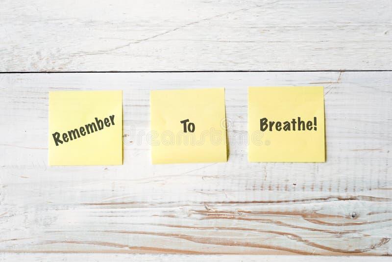 Tre note di Post-it gialle con il messaggio si ricordano respirare! fotografia stock libera da diritti