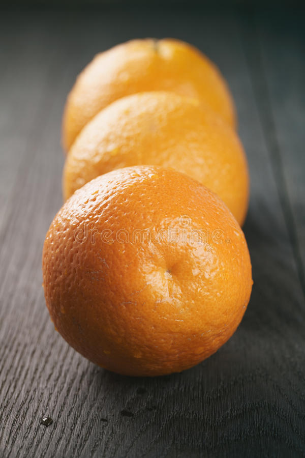 Tre nya mogna apelsiner på ekträtabellen royaltyfri fotografi