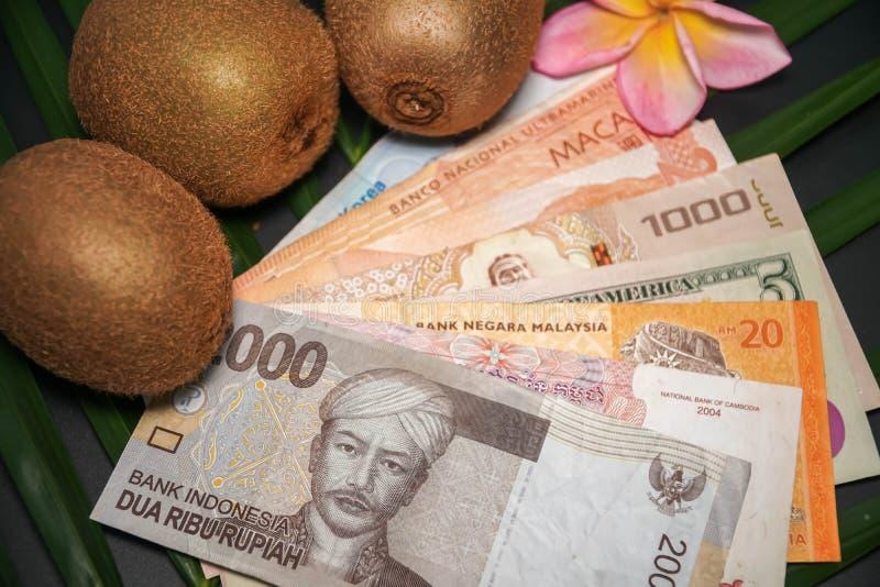 Tre nya rå exotiska tropiska Kiwi Fruits kallade också Kines Gooseberrys med internationella valutasedlar arkivfoton