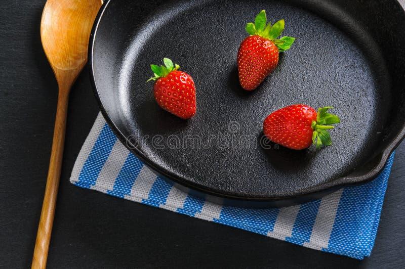 Tre nya röda jordgubbar på den svarta järn- pannan tjänade som med den träskeden och servetten Begrepp royaltyfri fotografi