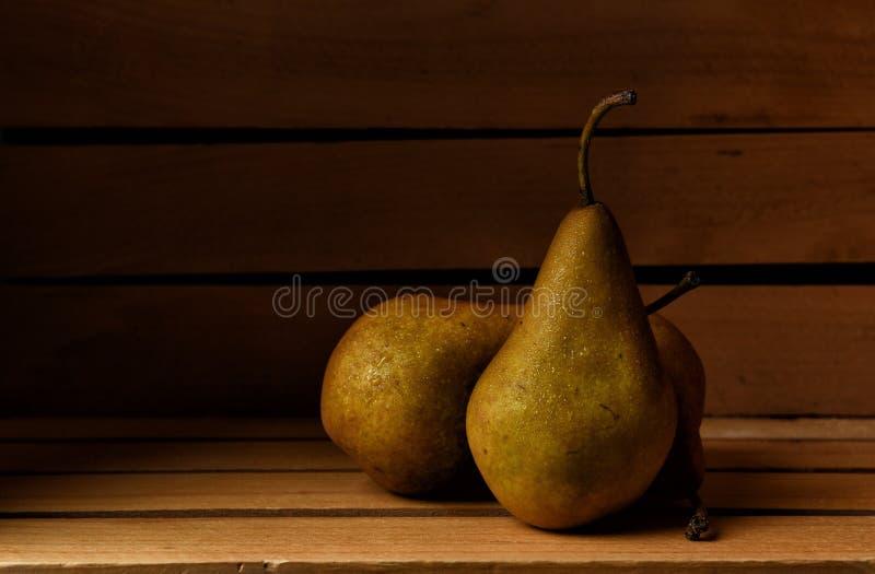 Tre nya valda Bosc päron i en träpackande spjällåda royaltyfria foton