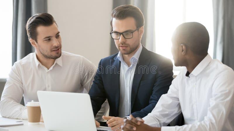 Tre olika affärsmän som arbetar tillsammans att samarbeta på bärbara datorn i regeringsställning arkivbilder