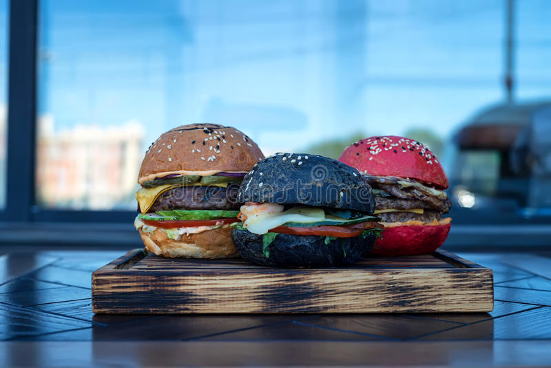 Tre olika hamburgare på träbräde royaltyfria bilder
