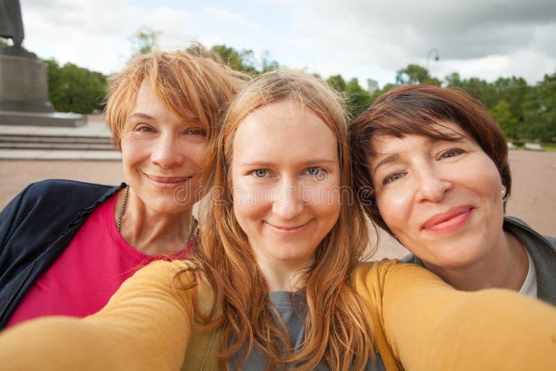 Tre olika lyckliga kvinnavänner som gör selfiefotoet och har rolig det fria royaltyfri fotografi