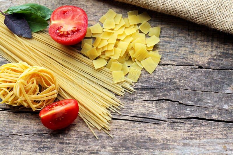 Tre olika typer av pasta med ny purpurfärgad och grön basilika och röda tomater på en träbakgrund med ett ställe för text royaltyfri foto