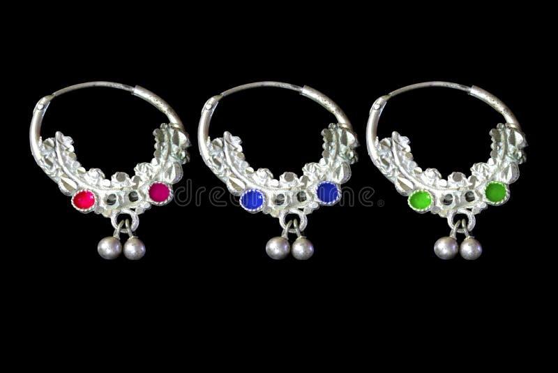 Tre orecchini d'argento su un fondo nero fotografia stock
