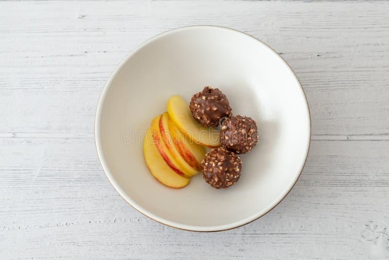 Tre palle ragruppate ricche di noci del gelato del cioccolato e Apple affettato in una ciotola servente marrone sui bordi di legn fotografia stock libera da diritti