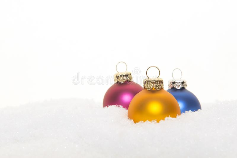 Tre palle variopinte della decorazione di natale in neve su un BAC bianco fotografia stock