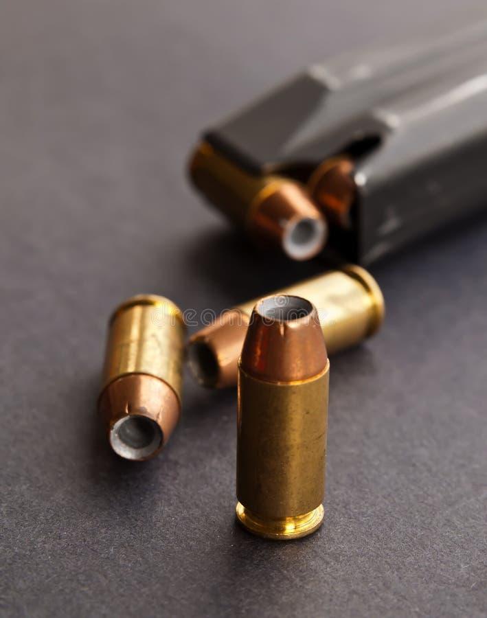 Tre pallottole vuote del punto accanto ad una rivista nera della pistola fotografia stock