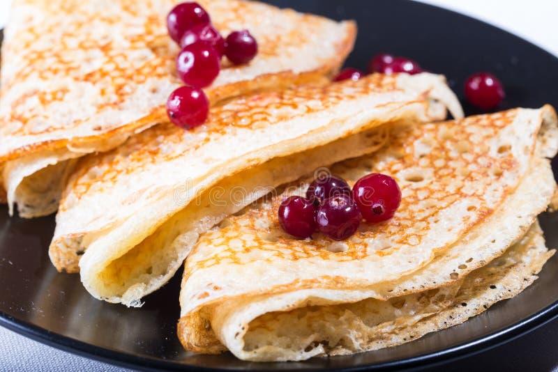 Tre pancake rubicondi su una banda nera con le bacche rosse immagini stock