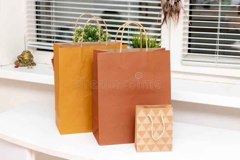 Tre pappers- shoppa påsar på den vita tabellen hemma, trendig kläder och skönhetsmedelköpbegrepp fotografering för bildbyråer