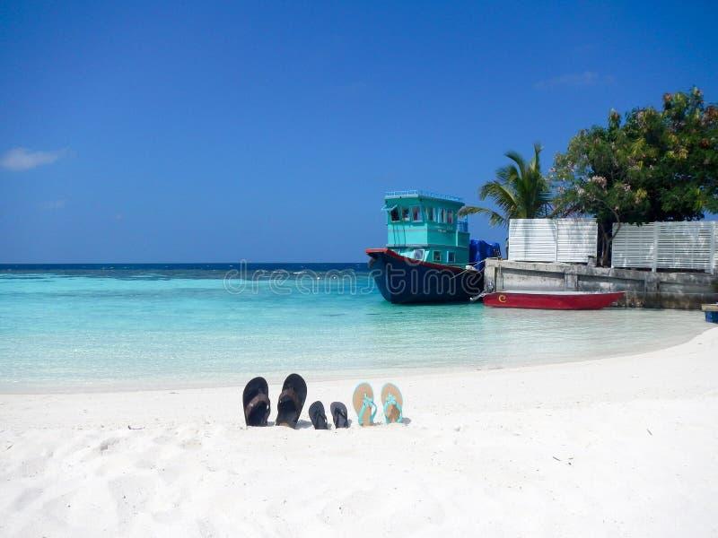 Tre par av sandaler för flipmisslyckanden på en Maldive strand propped upp i sanden med en gammal fiskebåt på en kaj bakom och gö royaltyfria bilder