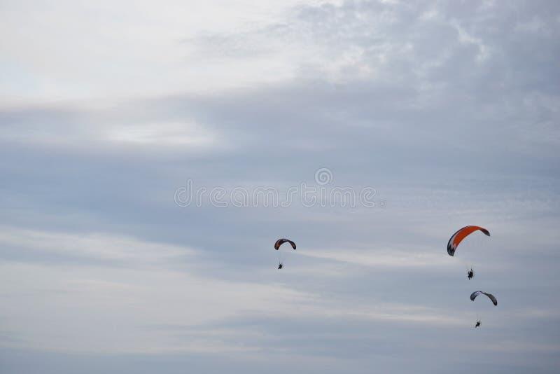Tre paragliders som långt borta flyger i en ljus molnig himmel i sommaren royaltyfri fotografi