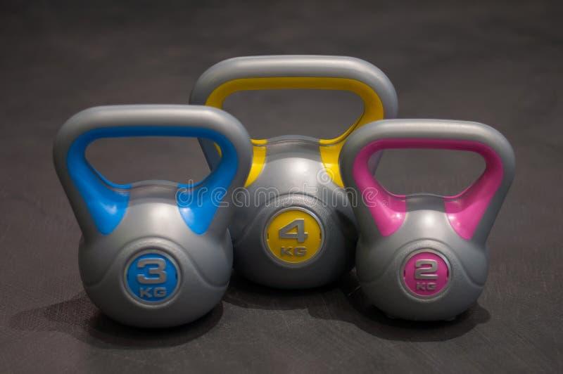 Tre parecchi pesi di plastica dei pesi e dei colori differenti fotografia stock