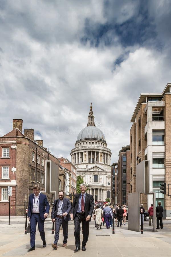 Tre passade affärsmän går nära St Pauls Cathedral arkivbilder