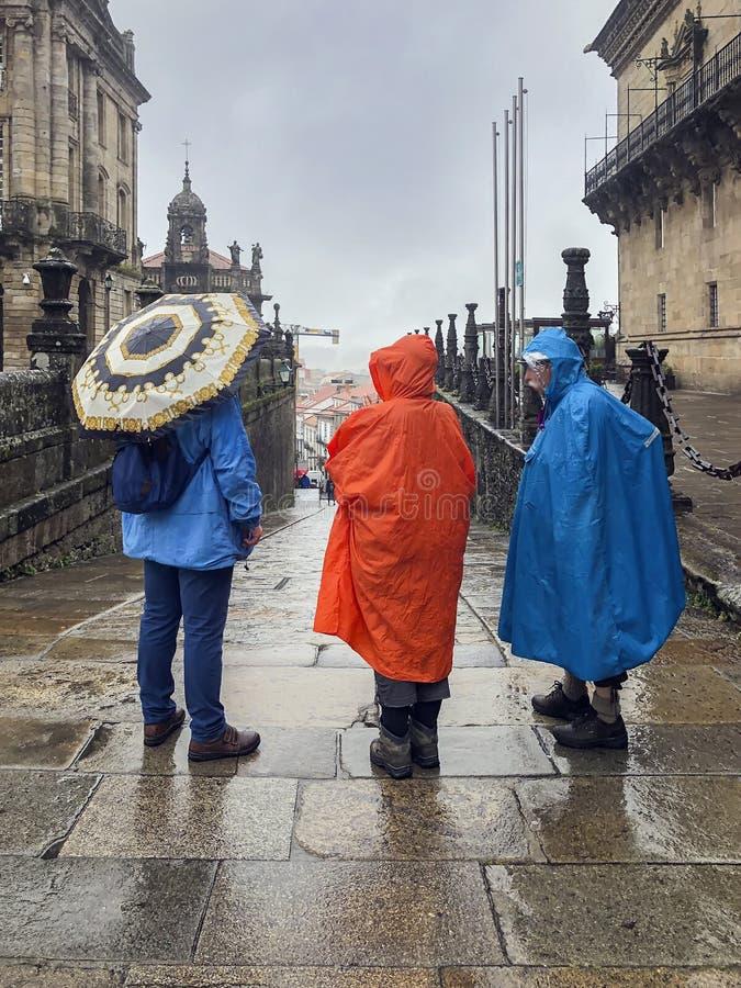Tre pellegrini di nuovo noi, con gli zainhi in impermeabili variopinti con una condizione degli ombrelli nel quadrato storico immagini stock