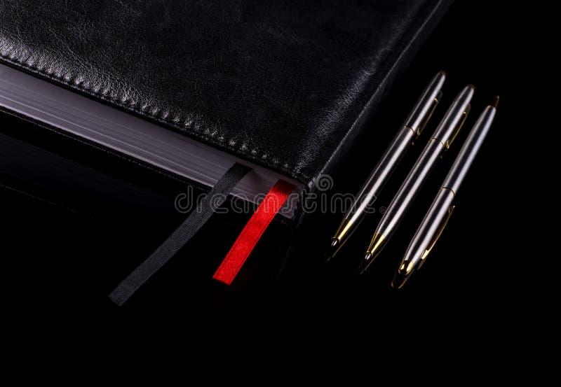 Tre penne vicino al taccuino su un fondo nero immagini stock