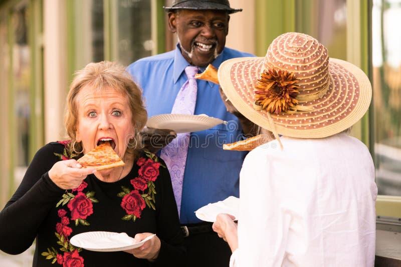 Tre pensionärer som äter gatamat arkivfoto
