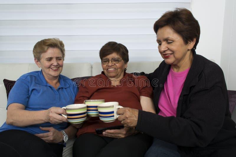 Tre pensionerade höga kvinnliga systrar som sitter på soffan arkivbilder