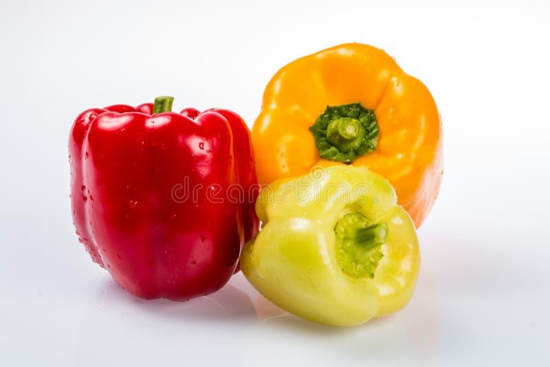 Tre peperoni bulgari maturi deliziosi, calce, rossa, arancia, con le code verdi nello stesso aereo su un fondo bianco immagini stock libere da diritti