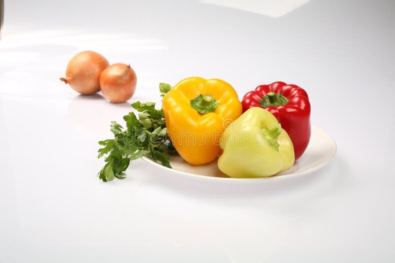Tre peperoni bulgari maturi deliziosi, calce, rosso, arancia e due cipolle su un piatto, su un fondo bianco fotografie stock libere da diritti