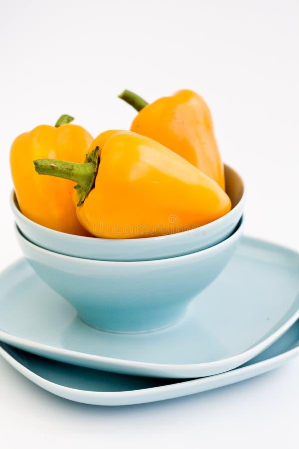 Tre peperoni dolci gialli sono sui piatti fotografia stock