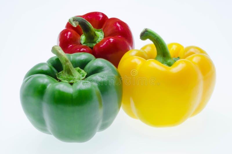 Tre peperoni dolci su un fondo bianco immagini stock
